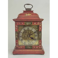 AN ANTIQUE RED LACQUERED BRACKET CLOCK