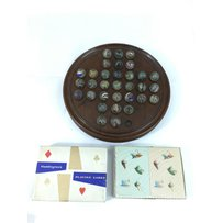 A wooden solitaire set with old spider twist marbles and a W…