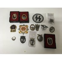 A box containing a collection of badges to include German ex…