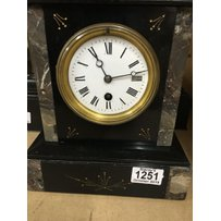 A slate mantle clock with Arabic numerals and a smaller slat…